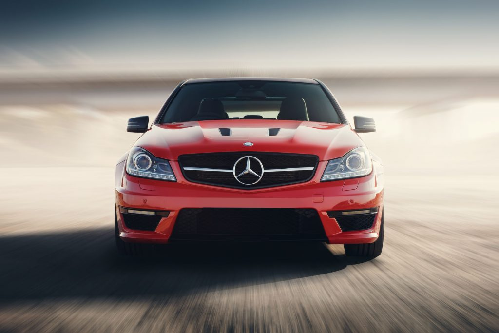aratov, russia - august 24, 2014: red sport car mercedes-benz c63 amg drive speed on asphalt road at sunset
